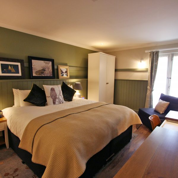Cosy Green Walled Boutique Hotel room with White Wardrobe