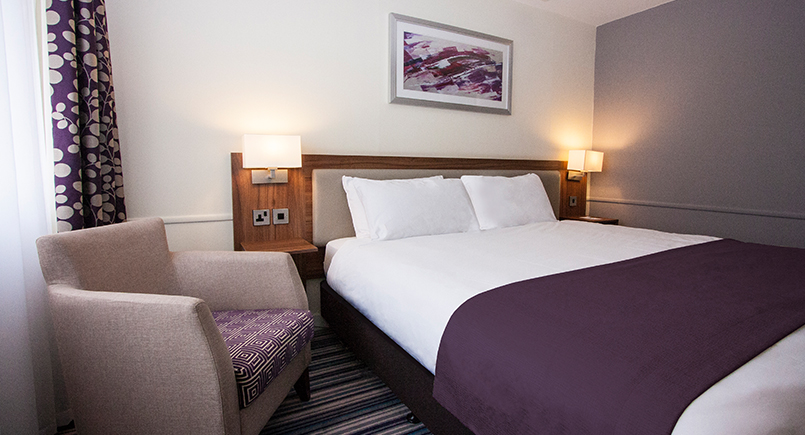 Holiday inn double hotel bedroom with wooden headboard