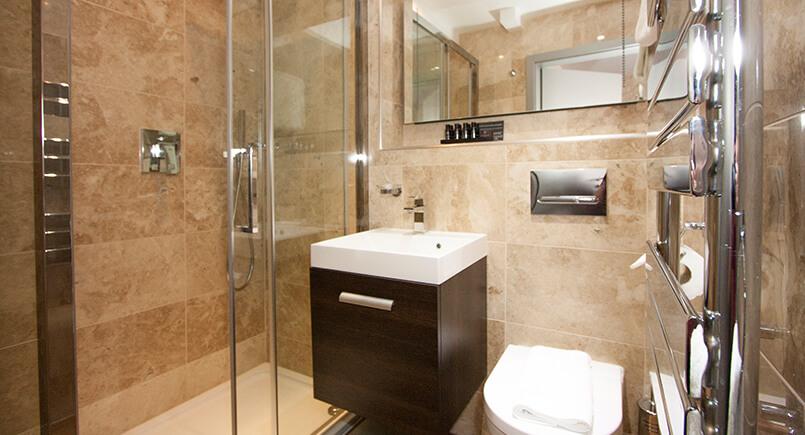 Hotel bathroom en-suite with dark wood cabinet