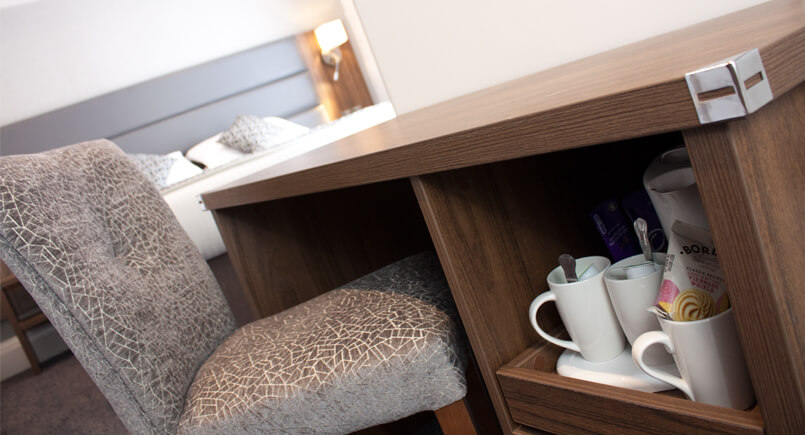 Brown wooden hotel desk with pull out tea and coffee draw