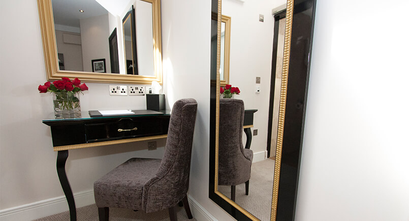 Black and gold hotel bedroom desk and mirror