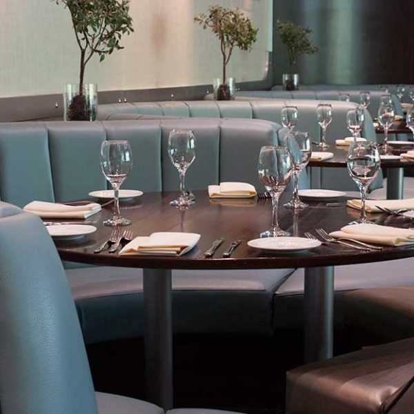 Curved banquette seating upholstered in soft green leather